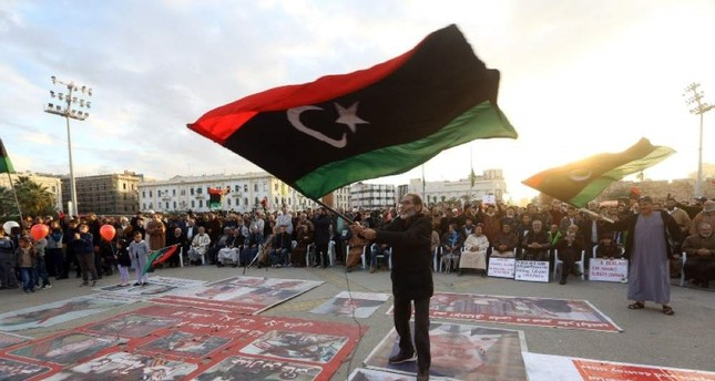 Demonstrators wave flags and step on posters of some world leaders as they take part in a rally against eastern Libyan strongman Khalifa Haftar in Tripoli on Jan. 10, 2020. AFP Photo