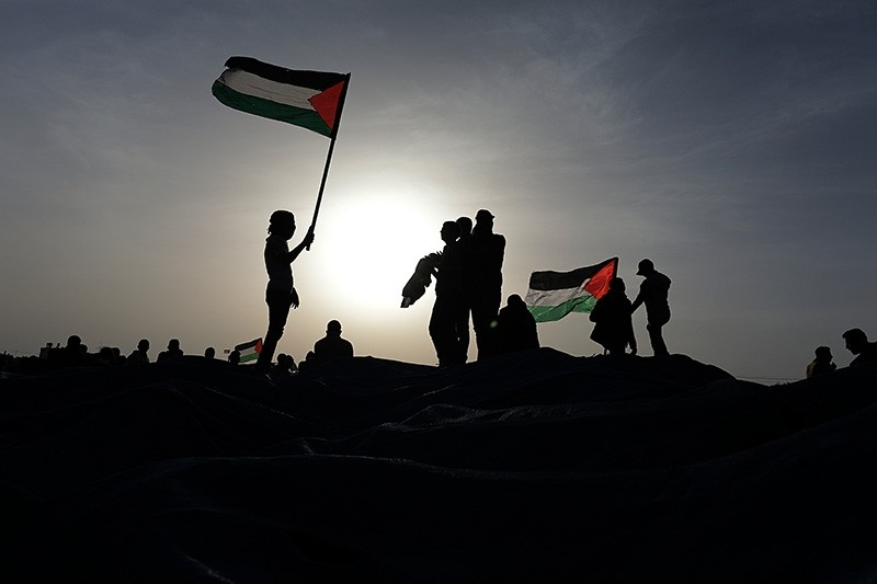 Protesters wave Palestinian flags during clashes with Israeli troops near the border with Israel in the east Khan Yonis town southern Gaza Strip on, 04 April 2018. (EPA Photo)