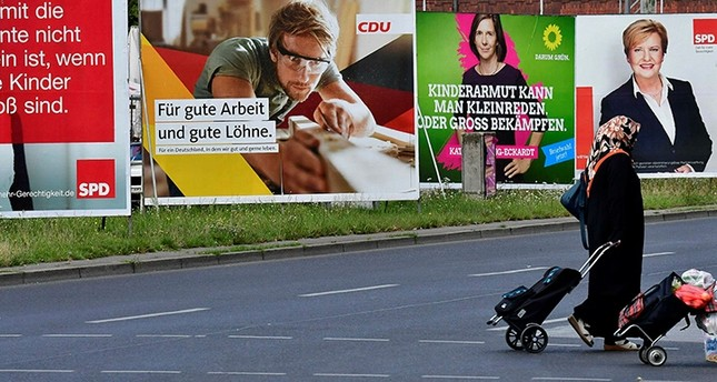 A woman wearing a hijab passes by several election banners for the upcoming September general elections in Berlin, Germany, Aug. 23, 2017. (AFP Photo)