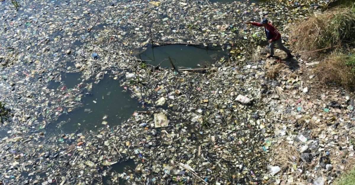 A scavenger collects plastic waste for recycling on the Citarum river choked with garbage and industrial waste, in Bandung, West Java province on June 26, 2019 (AFP Photo)