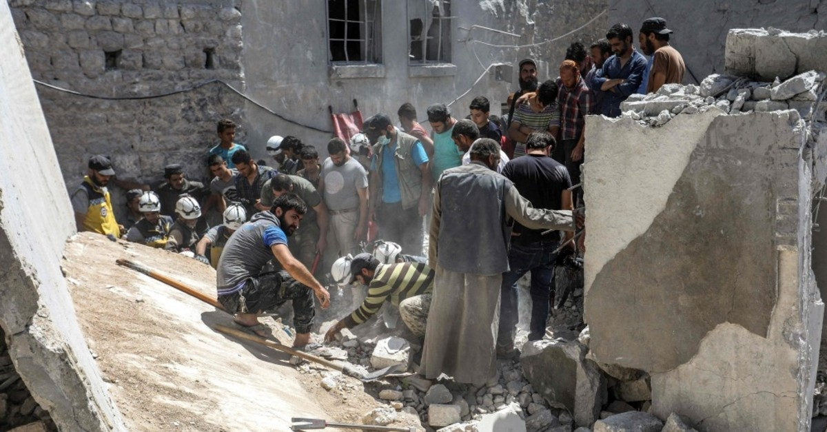 Members of the Syrian Civil Defence (White Helmets) search for bodies and survivors in a collapsed building following a reported regime airstrike, south of Syria's Idlib province, July 12, 2019.