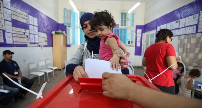 A woman carries a child as she casts her vote at a polling station during presidential election in Tunis, Tunisia Sept. 15, 2019. (Reuters Photo)