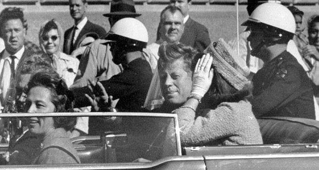 In this Nov. 22, 1963 file photo, President John F. Kennedy waves from his car in a motorcade approximately one minute before he was shot in Dallas (AP Photo)