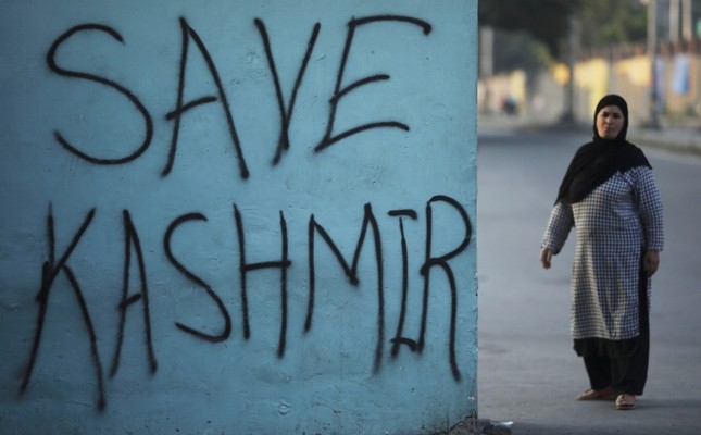 A woman stands next to a graffiti written on a wall during restrictions, following scrapping of the special constitutional status for Kashmir by the Indian government, in Srinagar, Jammu and Kashmir, India, Sept. 15, 2019. (Reuters Photo)