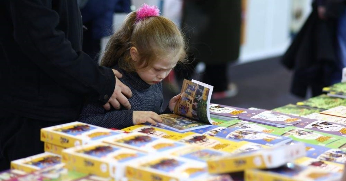 A child examines a book at the fifth CNR Book Fair. (Photo by Saffet Azak)