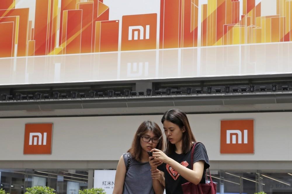 Two women use a smartphone outside a Xiaomi store in Hong Kong.