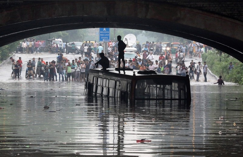 Indian men stand on top of a Delhi Transport Corporation bus, that is half submerged, on a water logged road during after heavy rain in New Delhi, India, July 16, 2018. (EPA Photo)