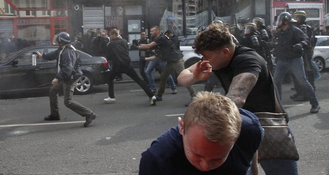 French police disperse a crowd of football hooligans in Lille, France.