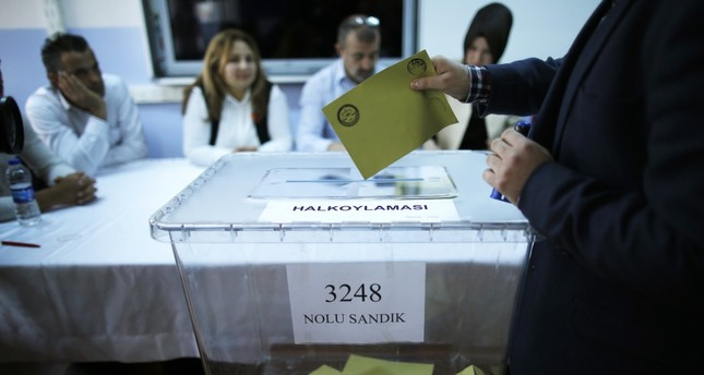 A voter casts a ballot inside a polling station in Istanbul, Sunday, April 16, 2017.