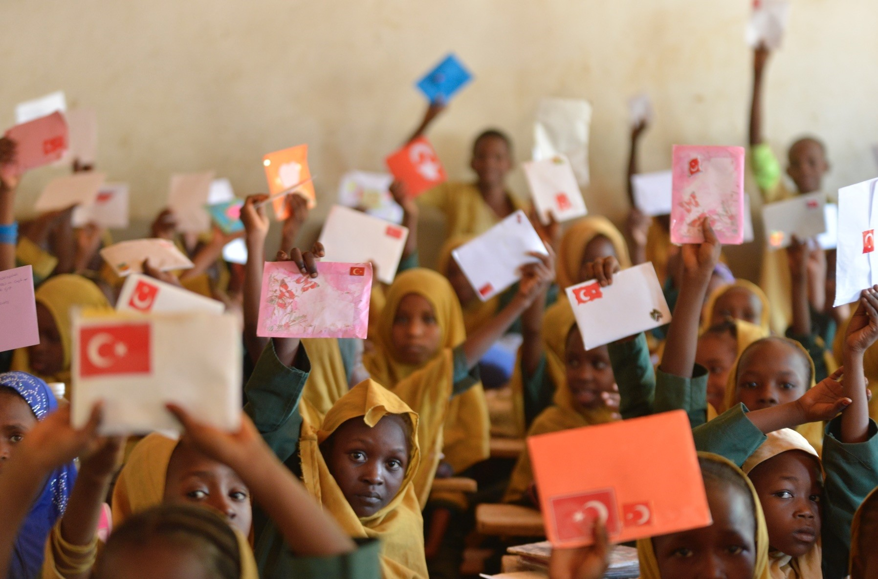 Children in Niger hold up the letters they received from their Turkish peers.