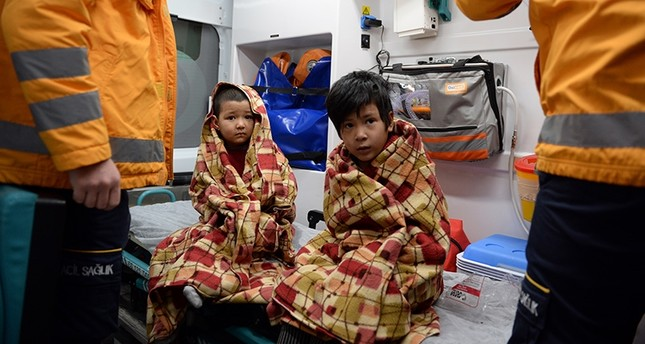 Mukaddese, 7, and Umit, 5, receive care from Turkish emergency services personnel after being rescued from their burning home in Tokat, Turkey. (AA Photo)