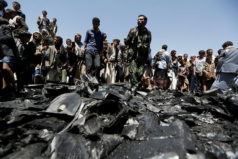 People gather at the site of the wreckage of a drone aircraft which the Houthi rebels said they have downed in Sanaa, Yemen October 1, 2017 (Reuters Photo)