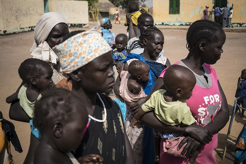In this photo taken Monday, March 13, 2017, mothers hold their children as they wait to have them screened for malnutrition at a UNICEF-supported Outpatient Therapeutic Program in Aweil, South Sudan (AP Photo)