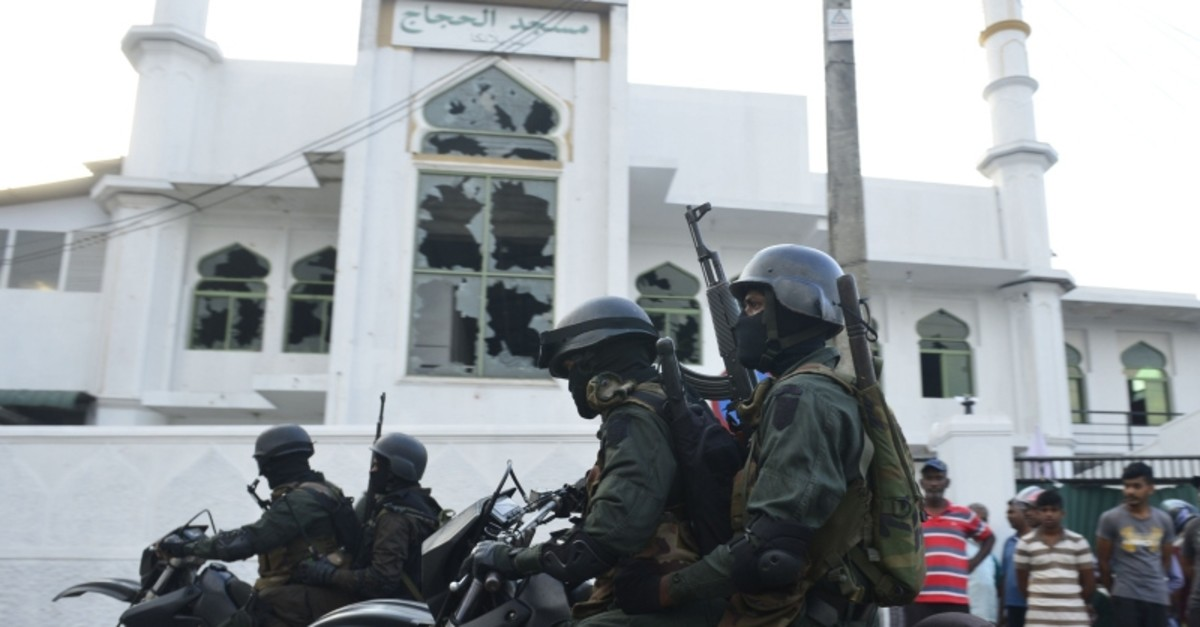 Heavily-armed Sri Lankan soldiers ride a motorcycle in front of the Jumha Mosque after a mob attack in Minuwangida on May 14, 2019. (AFP Photo)