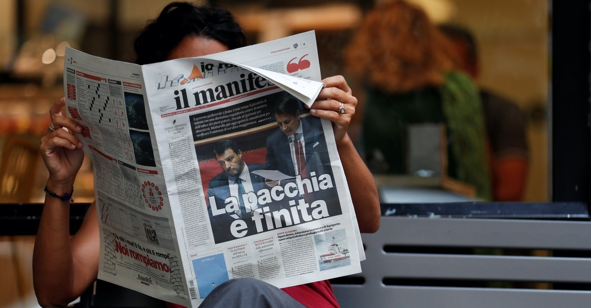 An Italian woman reads a newspaper with news of the government crisis and the resignation of Prime Minister Giuseppe Conte, Rome, Italy, Aug. 21, 2019.