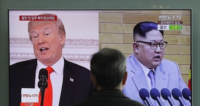 A man watches a TV screen showing file footages of U.S. President Donald Trump, left, and North Korean leader Kim Jong Un, right, during a news program at the Seoul Railway Station in Seoul (AP File Photo)
