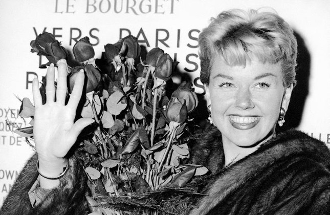 In this April 15, 1955 file photo, American actress and singer Doris Day holds a bouquet of roses at Le Bourget Airport in Paris, France after flying in from London. AP Photo