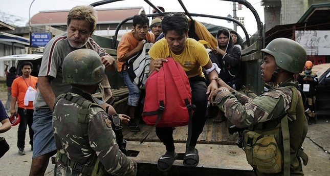 Filipino villagers who were trapped in the fighting between Daesh terrorists and government forces, are escorted by soldiers following their escape to freedom in Marawi City, June 03, 2017 (EPA Photo)