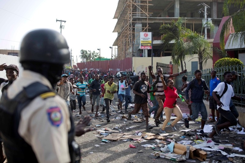 A police officer looks on as a crowd enters the Delimart supermarket complex, which had been burned during two days of protests against a planned hike in fuel prices in Port-au-Prince, Haiti, Sunday, July 8, 2018. (AP Photo)