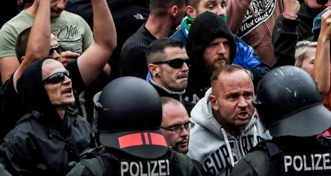 Right wing protesters gesture towards police in riot gear as they gather at the place where a man was stabbed in the night of the 25 August 2018, in Chemnitz, Germany, 27 August 2018. (EPA Photo)