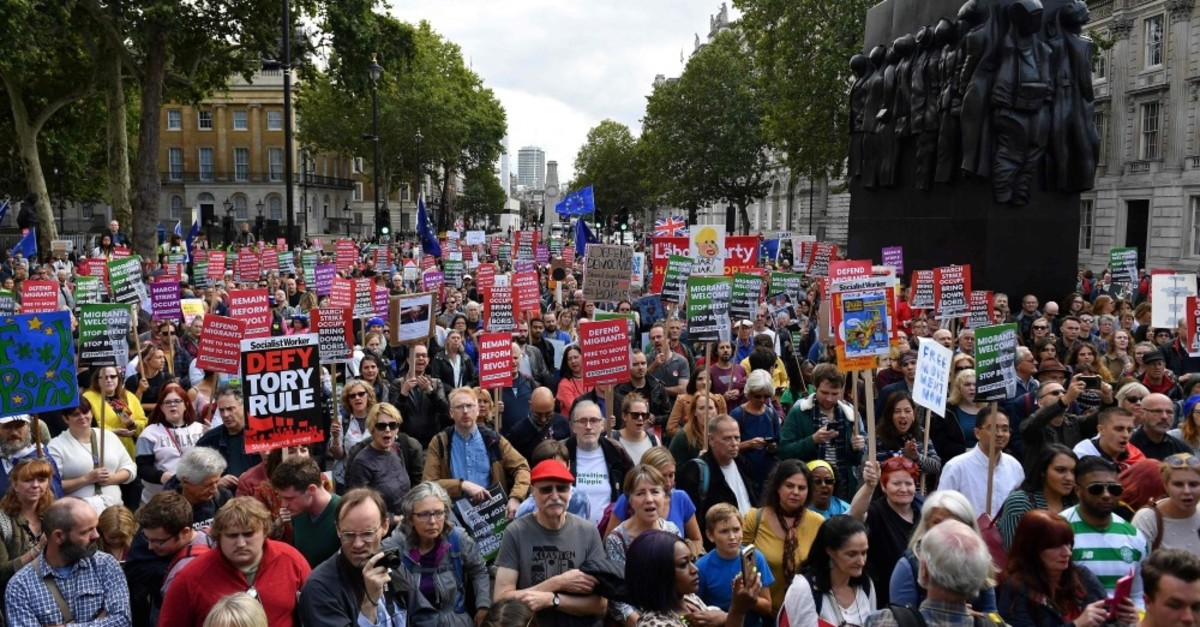 Demonstratiors hold placards and wave EU flags during an anti-government protest calling for British Prime Minister Boris Johnson's resignation, outside Downing Street, London, Sept. 7, 2019.