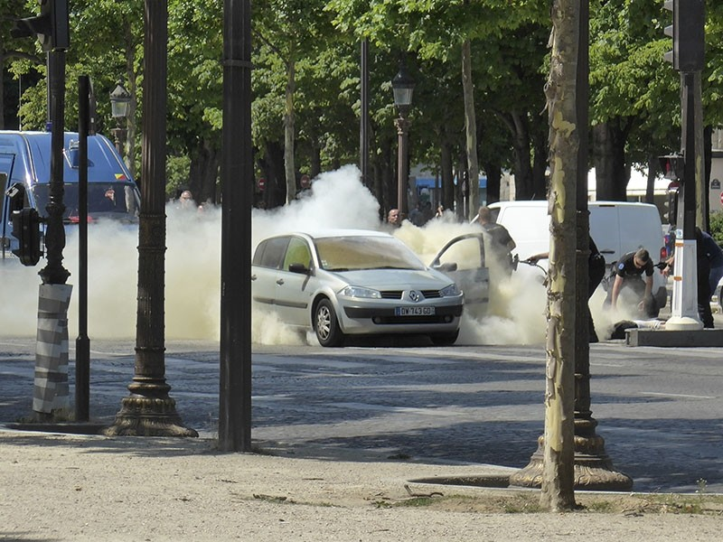 In this photo provided by Noemie Pfister, French gendarmes use fire extinguishers after a man rammed into a police convoy and detonated an explosive device on the Champs Elysees avenue in Paris, France, Monday, June 19, 2017. (Noemie Pfister via AP)