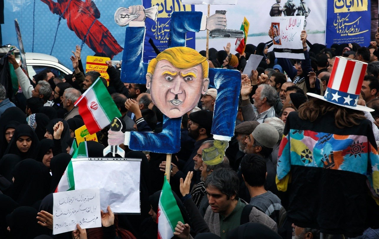 Iranians hold a placard showing a caricature of U.S. President Donald Trump during an anti-U.S. demonstration marking the 39th anniversary of U.S. Embassy takeover, in front of the former U.S. Embassy in Tehran, Iran, Nov. 4.