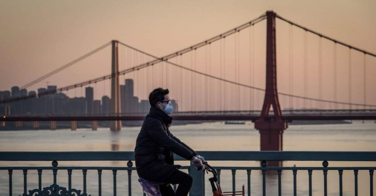 A man wearing a protective face mask rides a bicycle in Wuhan in China's central Hubei province, Feb. 17, 2020. (AFP Photo)