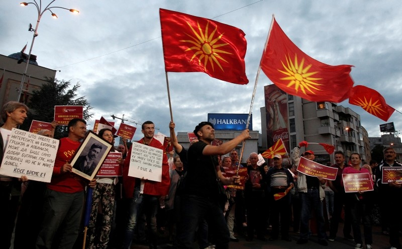 Opponents of the deal between Greece and Macedonia on the latter country's new name ,North Macedonia, hold banners and wave the former national flag, while protesting outside the parliament in Skopje, Macedonia, Saturday, June 23, 2018.  (AP Photo)