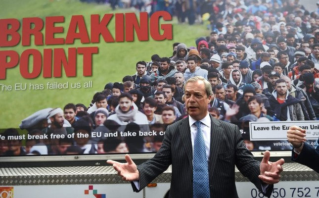 "Former United Kingdom Independence Party UKIP member Nigel Farage poses in front of the official ""leave"" campaign poster of his party, June 16, 2016."