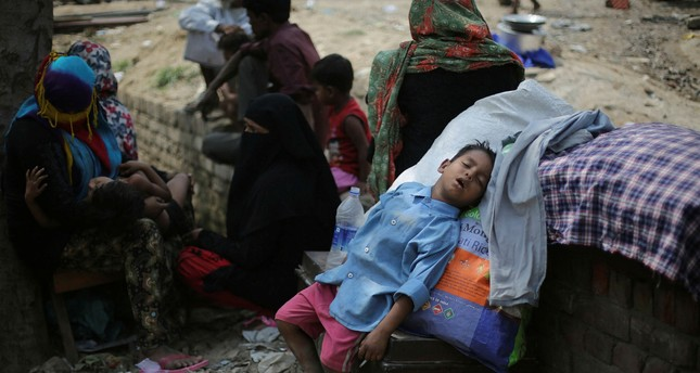 A boy naps under the shade of a tree after an early Sunday fire razed down a Rohingya camp in the Kalindi Kunj area of New Delhi, April 15.