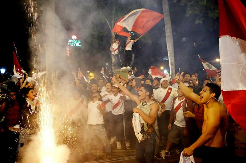 Fans celebrate after Peru qualified for the first time in 36 year for the soccer World Cup, in downtown Lima, Peru, Nov. 15, 2017. (AP Photo)