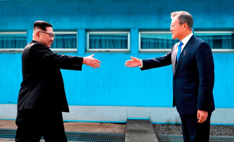 In this April 27, 2018, file photo, North Korean leader Kim Jong Un, left, prepares to shake hands with South Korean President Moon Jae-in over the military demarcation line at the border village of Panmunjom in Demilitarized Zone. (AP Photo)