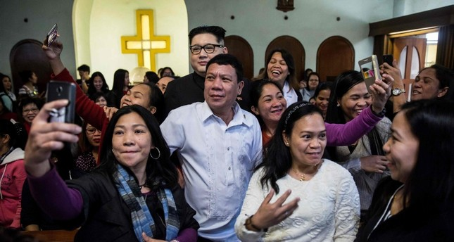 A Philippine President Rodrigo Duterte impersonator, who goes by the name Cresencio Extreme, and a North Korean leader Kim Jong Un impersonator, who goes by the name Howard X, attend a church service in Hong Kong, Feb. 3, 2019. (AFP Photo)