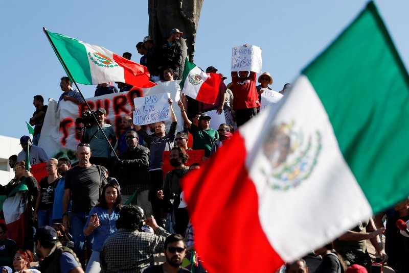 Demonstrators holding a placard that read, ,Not to the invasion, and waving Mexican flags, attend a protest against migrants who are part of a caravan traveling en route to the United States, in Tijuana, Mexico November 18, 2018. (Reuters Photo)
