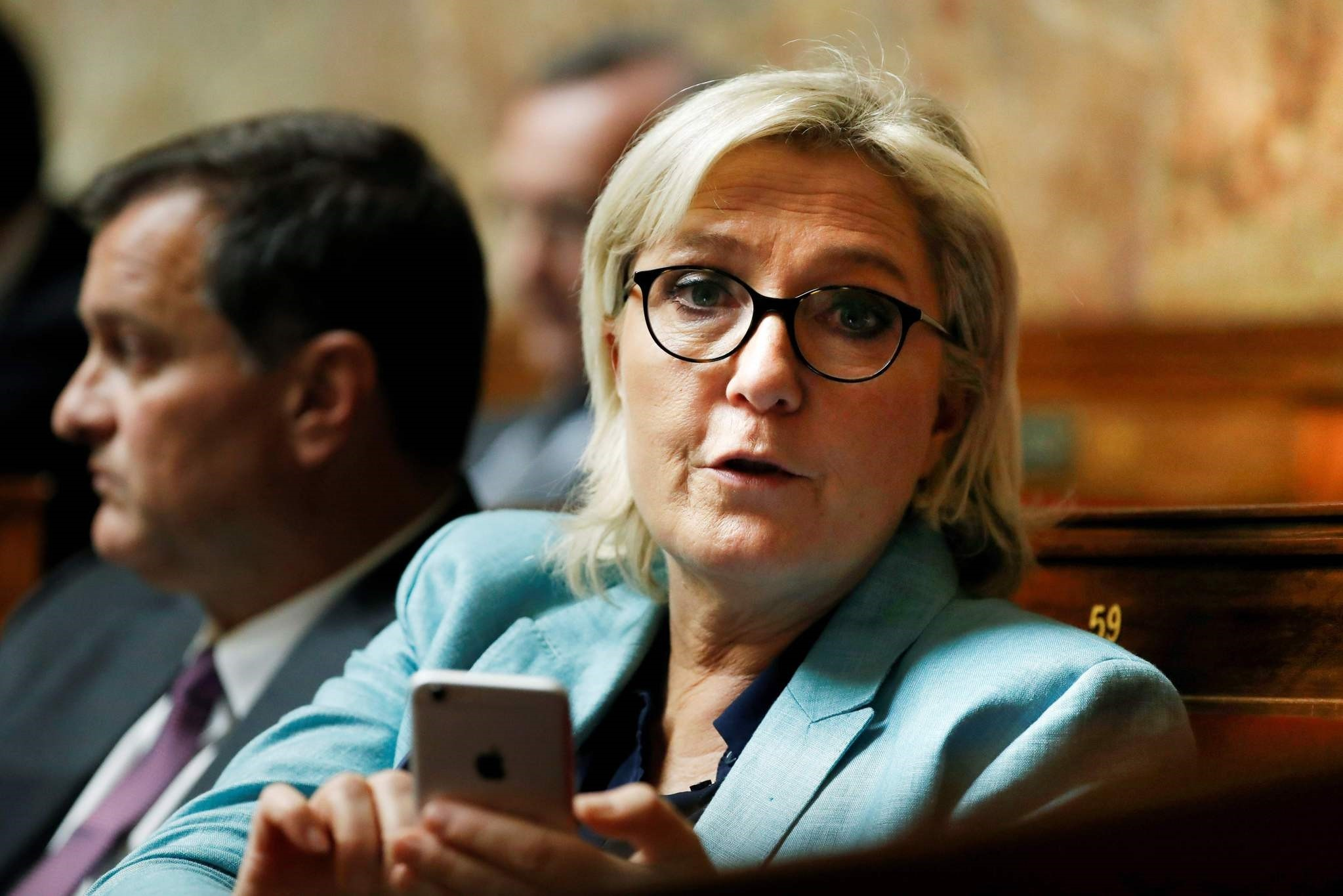 This file photo taken on Oct. 17, 2017 shows FN party leader Le Pen holding her mobile phone as she attends a session of questions to the government at the French National Assembly. (AFP Photo)