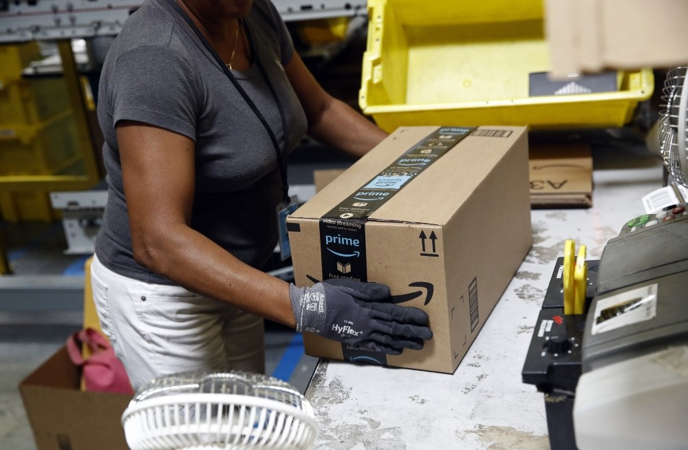A worker applies tape on a package before shipment at an Amazon fulfillment center in Baltimore, Maryland.
