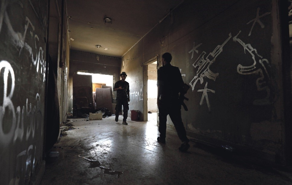 Terrorists from the U.S.-backed Syrian Democratic Forces (SDF) walk in an abandoned building where they are resting in the eastern al-Sanaa neighborhood, Raqqa, Aug. 13.