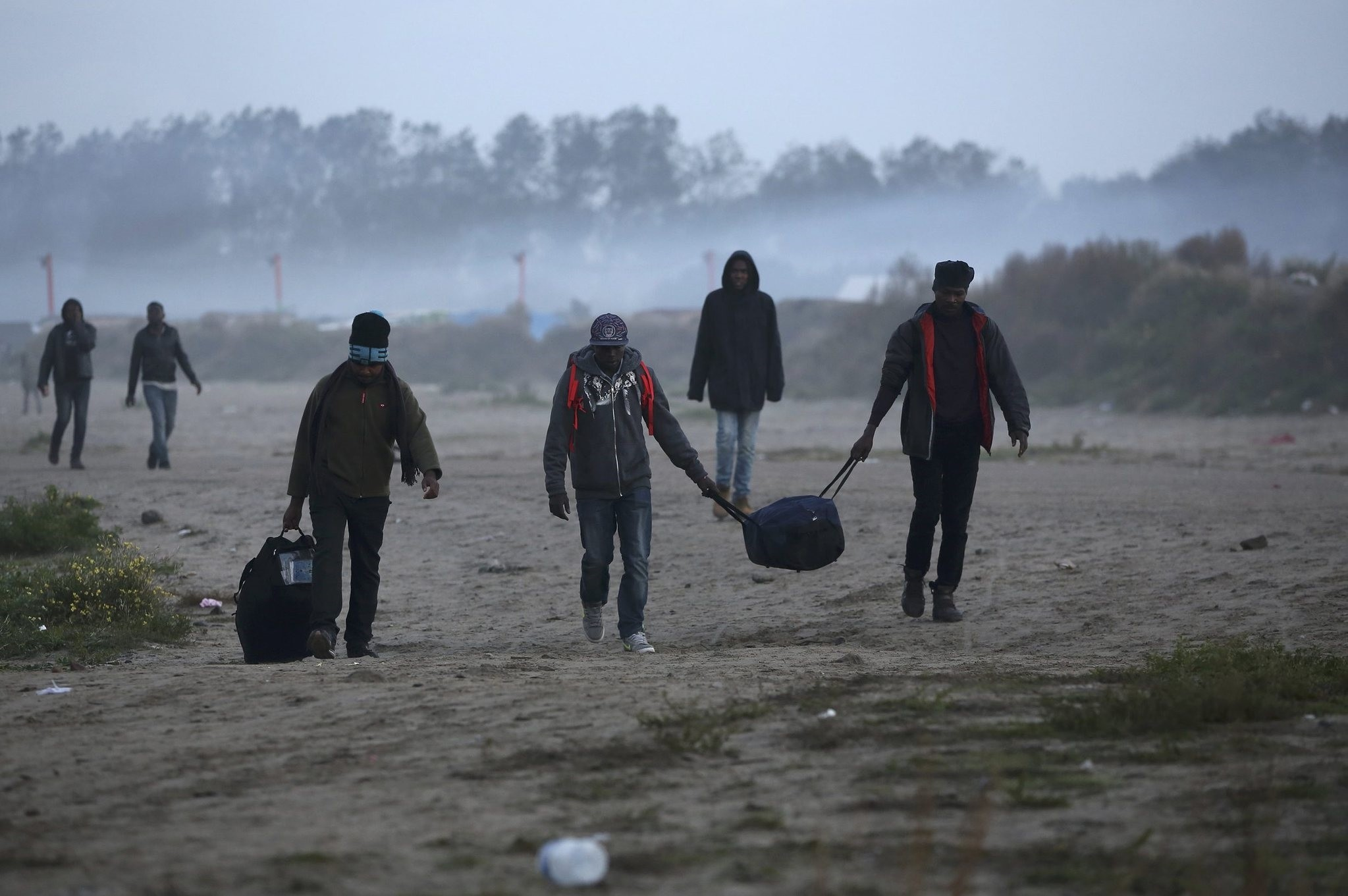 Migrants carry their belongings after evacuating a migrant camp, Calais, Oct. 25, 2016.