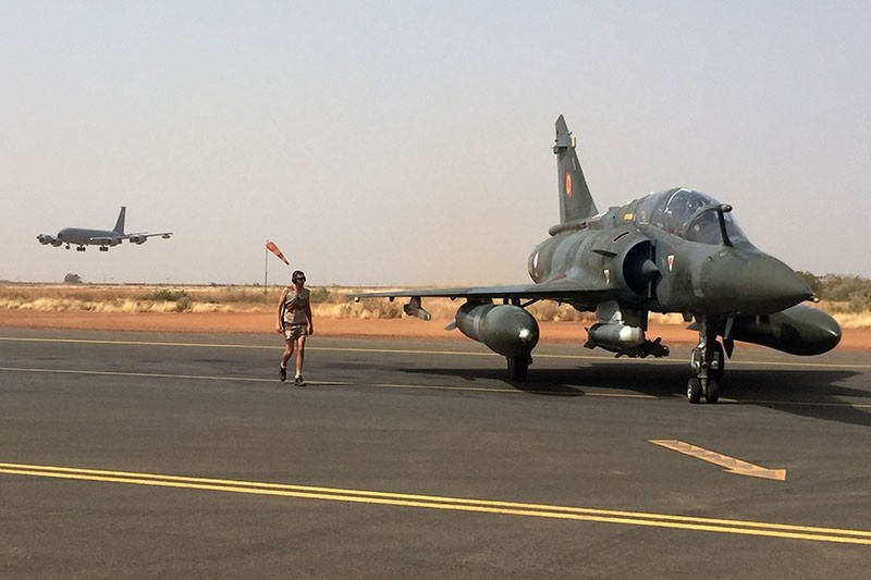 A soldier of the France's Barkhane mission sits in the cockpit of a French Mirage 2000 (R) as a C135 supply plane (back-L) prepares to land in a French military base in Niamey, Niger, on November 6, 2017. (AFP Photo)