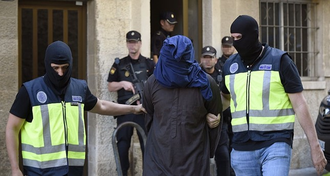Policemen escort a suspect that was arrested as part of an international police operation against Daesh, in Palma Majorca, the Balearic Islands, Spain, on June 28, 2017. (EPA Photo)