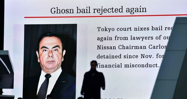 A pedestrian walks past an electric board showing a news program displaying a picture of former Nissan chief Carlos Ghosn in Tokyo on January 22, 2019 (AFP Photo)
