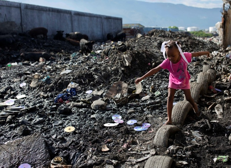 In this Nov. 21, 2017, file photo a girl returns from a designated area where neighbors use the bathroom outside, in the Cite Soleil slum of Port-au-Prince, Haiti. (AP Photo)