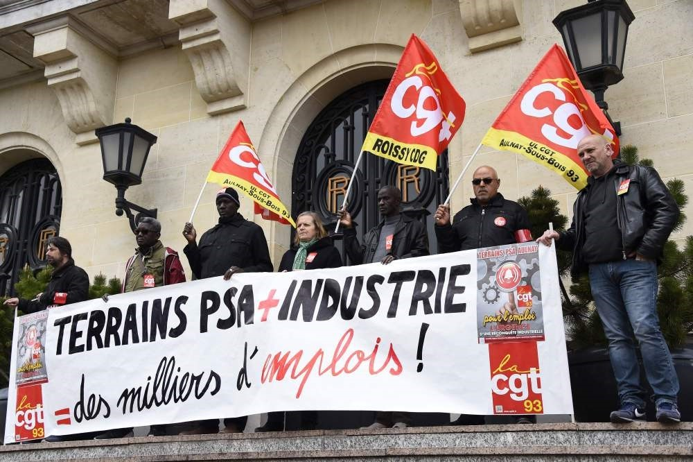 Employees of PSA Peugeot Citroen, hold a banner during a demonstration organised by CGT Union to call to preserve jobs and ask for the reindustrialisation of PSA plant in Aulnay-sous-Bois.The banner reads: u201cPSA fields + industry = thousands of jobsu201d.