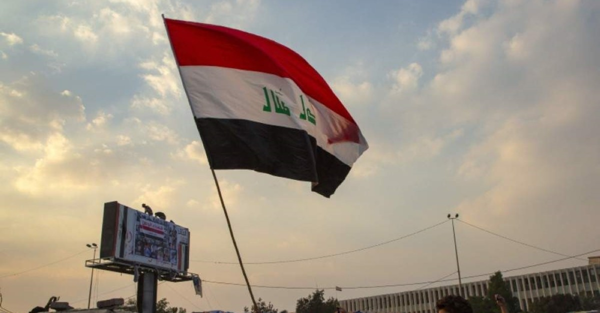 An Iraqi anti-government protester waves a national flag during a demonstration near the Basra governorate headquarters in the eponymous southern city, on Jan. 31, 2020. (AFP Photo)