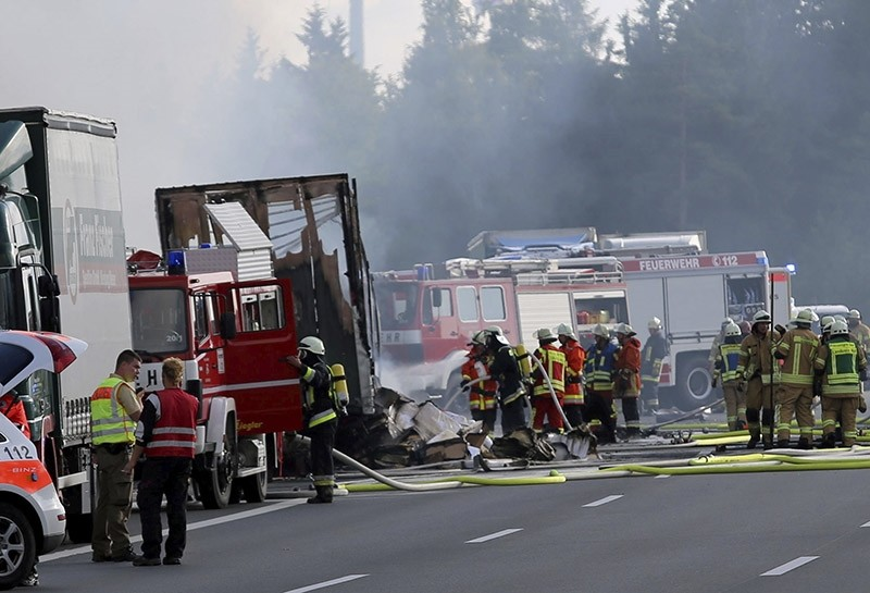 Rescue workers stand beside burnt-out coach on the motorway A9 near Muenchberg, southeastern Germany, Monday, July 3, 2017 after a bus crashed into a truck and caught fire. (AP Photo)