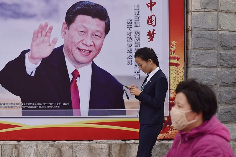 People walk past a poster featuring Chinese President Xi Jinping with a slogan reading ,Chinese Dream, People's Dream, beside a road in Beijing, China, Oct. 16, 2017. (AFP Photo)