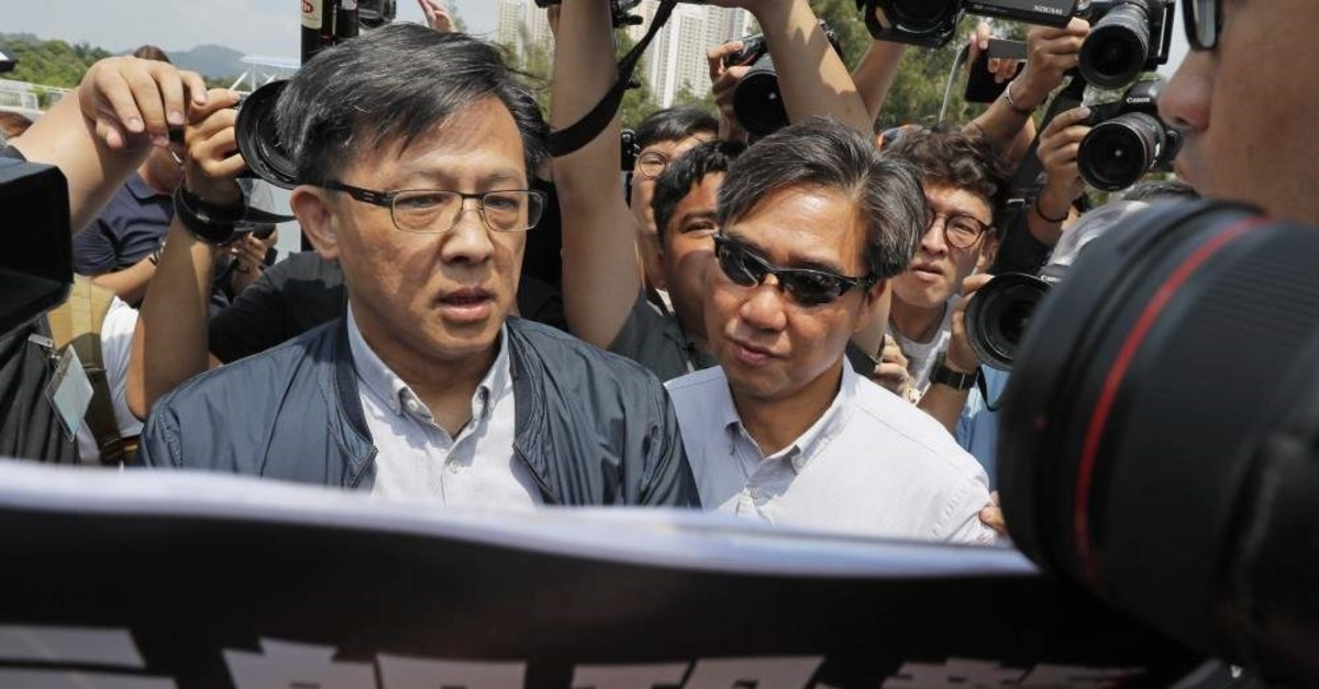 In this Aug. 12, 2019, photo, pro-Beijing lawmaker Junius Ho, left, attends a demonstration of an anti-riot vehicle equipped with water cannon at the Police Tactical Unit Headquarters in Hong Kong. (AP Photo)