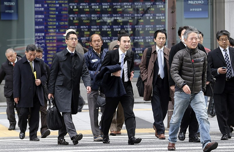 In this Dec. 9, 2013 file photo, people walk by an electronic stock board of a securities firm in Tokyo. (AP Photo)