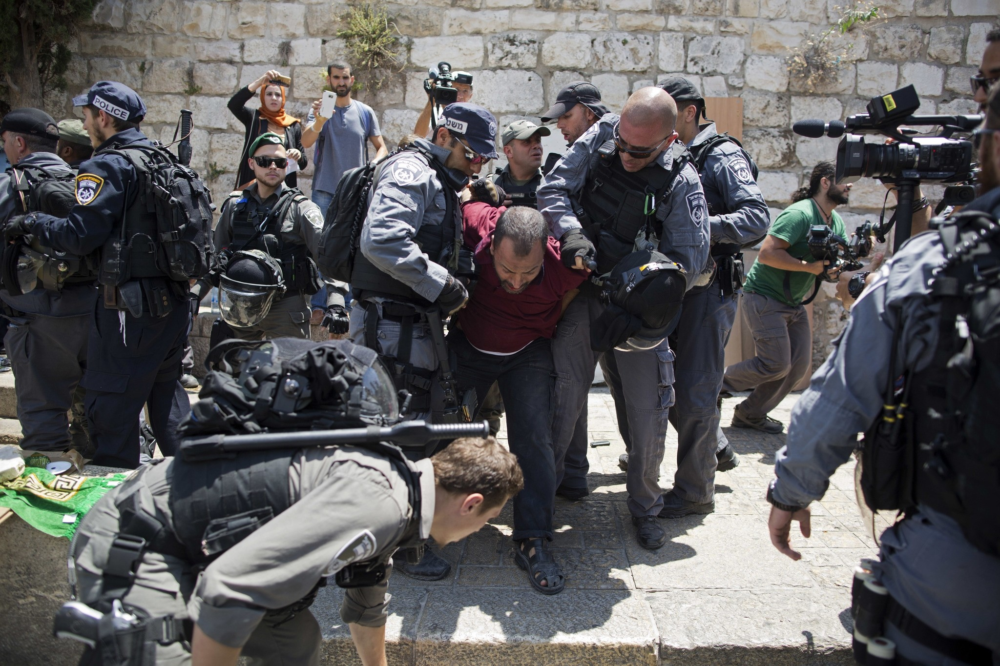 Israeli police officers detain a Palestinian man outside the Lion's Gate, following an appeal from clerics to pray in the streets instead of the Al Aqsa Mosque compound, in Jerusalem's Old City, Wednesday, July 19, 2017. (AP Photo)